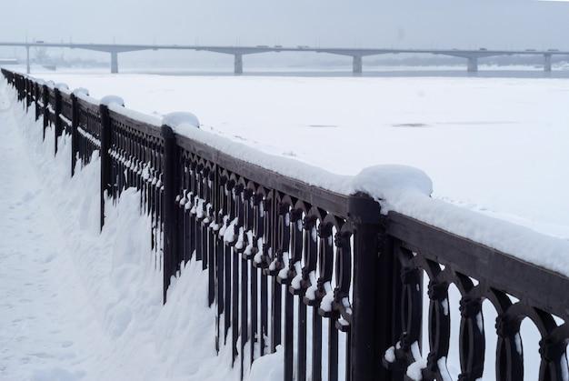 Замерзшая река и забор на набережной кастирона на фоне вечернего пасмурного снежного неба