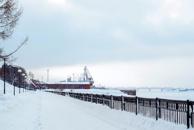 Замерзшая река с железнодорожным мостом, вдалеке грузовой порт и набережная
