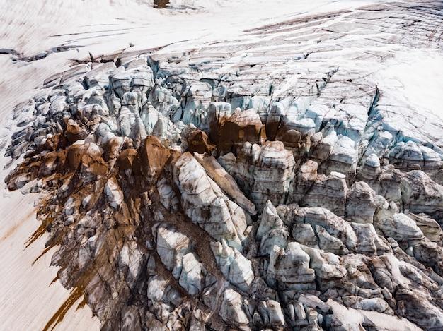 산 정상에 눈과 얼음으로 덮인 얼어 붙은 모래 형성, 밝은 태양 조명