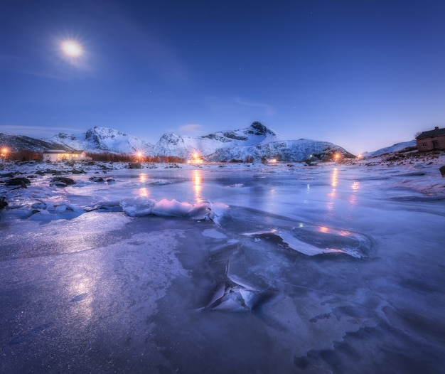 Frozen sea coast, beautiful snow covered mountains and starry sky with moon in winter at night. beautiful fjord in lofoten islands, norway. nordic landscape with ice, rocks, buildings, illumination