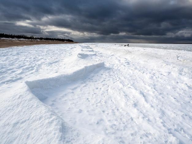 눈과 극적인 구름과 해안선과 얼어 붙은 바다.