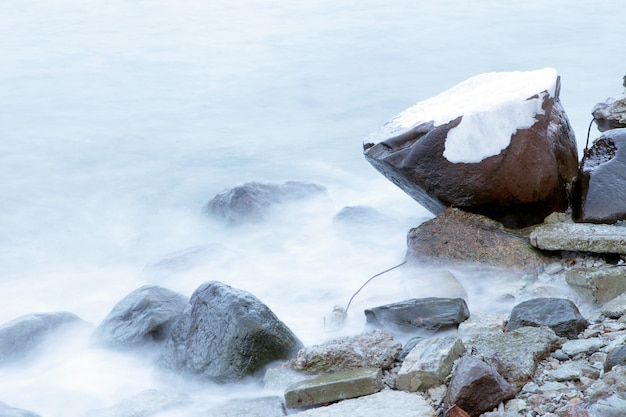 폭풍우 시간에 돌에 얼어 붙은 바닷물