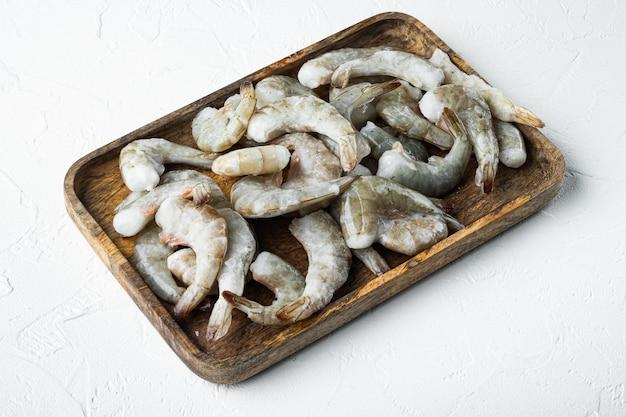 タイガーエビまたはアジアのタイガーシュリンプセットの冷凍シェル、木製トレイ、白い石の表面