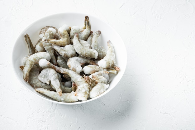 Frozen shell on tiger prawns or asian tiger shrimps set, on white stone  surface, with copy space for text