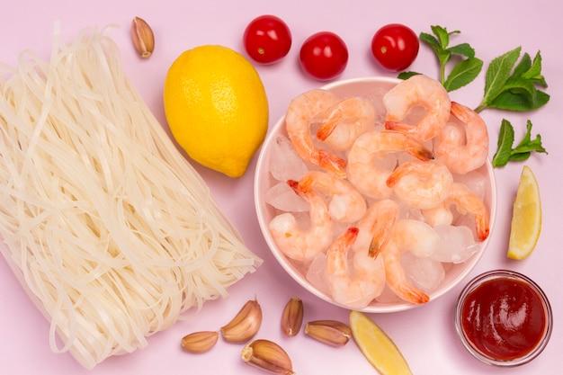 Замороженные креветки и лед в розовой миске. рисовая лапша, лимон, мята, чеснок, томатный соус.