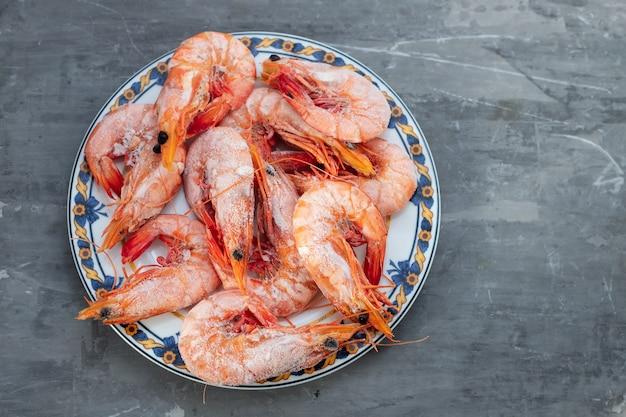 Frozen shrimps on plate on ceramic background