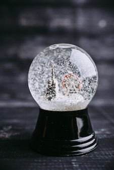 Frozen snow globe christmas magic ball with flying snowflakes and church and attraction.
