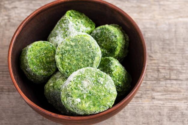 Frozen spinach on wooden background.