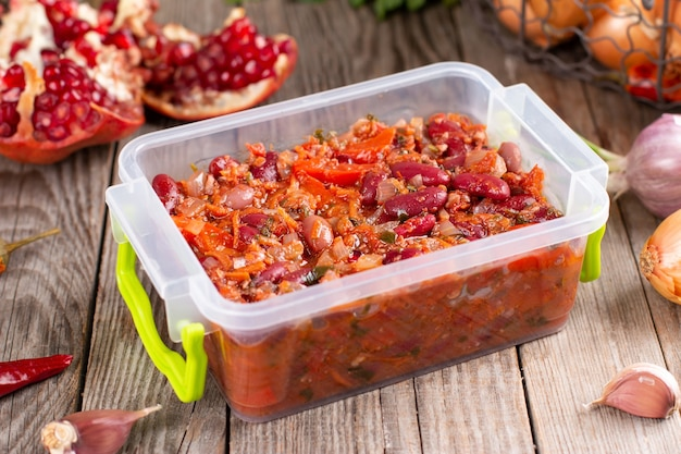 木製のテーブルの上の容器にトマトソースで煮込んだ小豆の冷凍