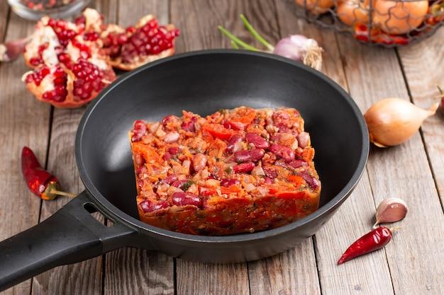 木製テーブルのフライパンの袋にトマトソースで煮込んだ小豆の冷凍