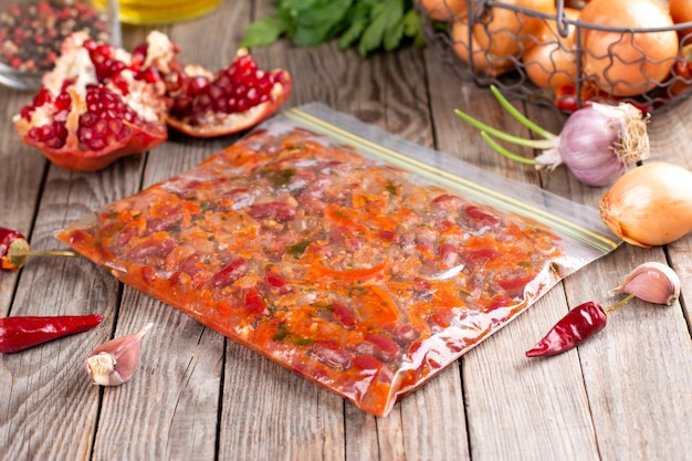木製テーブルの袋にトマトソースで煮込んだ小豆の冷凍