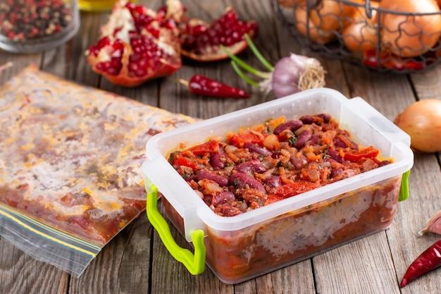 木製のテーブルの上にトマトソースで煮込んだ小豆の冷凍