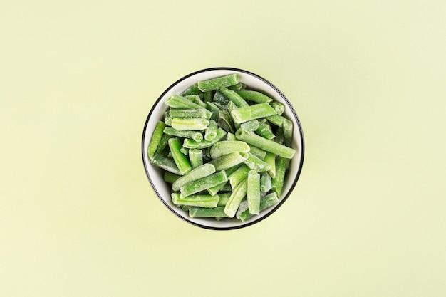Замороженная фасоль на зеленом столе