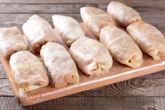 冷凍キャベツの詰め物をまな板で解凍します。半製品の準備。伝統的な料理。冷凍食品。