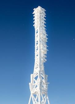 Замороженная телевизионная или сотовая вышка в сильном снегопаде возле лыжного центра башни радиосвязи с тарелкой и передвижной антенной против голубого неба в горах зимы.