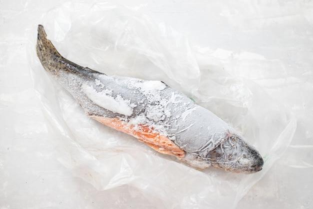 Замороженная форель на полиэтиленовом пакете на керамическом фоне