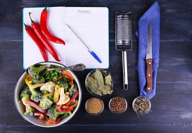 Замороженные овощи и пустой блокнот, на поверхности деревянного стола