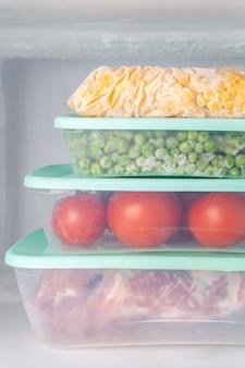 Замороженные овощи и мясо в синих пластиковых контейнерах
