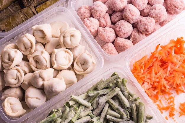 Замороженные овощи и мясные полуфабрикаты в пластиковых контейнерах на белой тарелке. фрикадельки, пельмени, нарезанная фасоль и тертая морковь