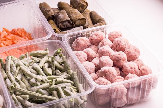 Замороженные овощи и мясные полуфабрикаты в пластиковых контейнерах на белой тарелке. тефтели, пельмени, долма в виноградных листьях, нарезанная фасоль и тертая морковь