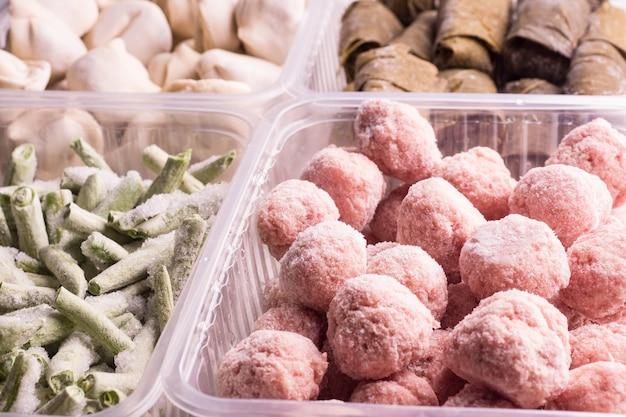 Замороженные овощи и мясные полуфабрикаты в пластиковых контейнерах на белой тарелке. тефтели, пельмени, долма в виноградных листьях, нарезанная фасоль