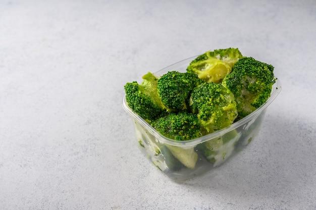 회색 표면 선택적 초점 개념 다이어트에 플라스틱 쟁반에 냉동 야채 브로콜리와