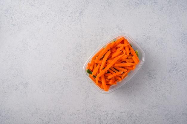 회색 표면 개념 다이어트와 건강한 식습관에 플라스틱 트레이에 냉동 야채 당근