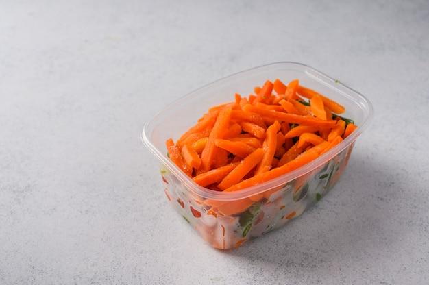 회색 표면 선택적 초점 개념 다이어트에 플라스틱 트레이에 냉동 야채 당근 및
