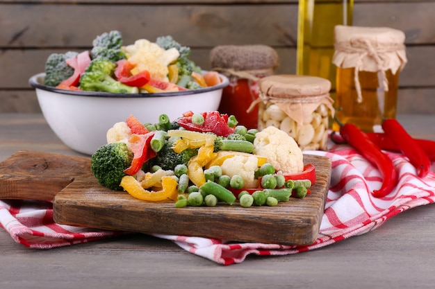 Frozen vegetables on cutting board, on napkin, on wooden table