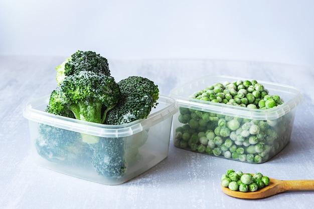 냉동 야채. 플라스틱 상자에 냉동 브로콜리와 완두콩과 회색 테이블에 나무 숟가락