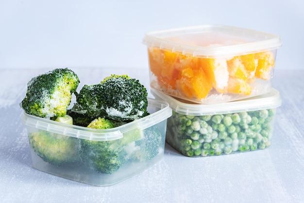 냉동 야채. 회색 테이블에 플라스틱 상자에 냉동 브로콜리, 완두콩, 호박
