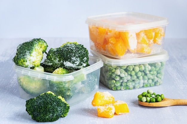 Frozen vegetables. frozen broccoli, peas and pumpkin in plastic boxes and a wooden spoon on grey table