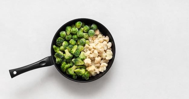 Замороженные овощи в сковороде на белом фоне. капустная смесь. брокколи, цветная капуста, брюссельская капуста. копирование пространства, вид сверху, плоская планировка.