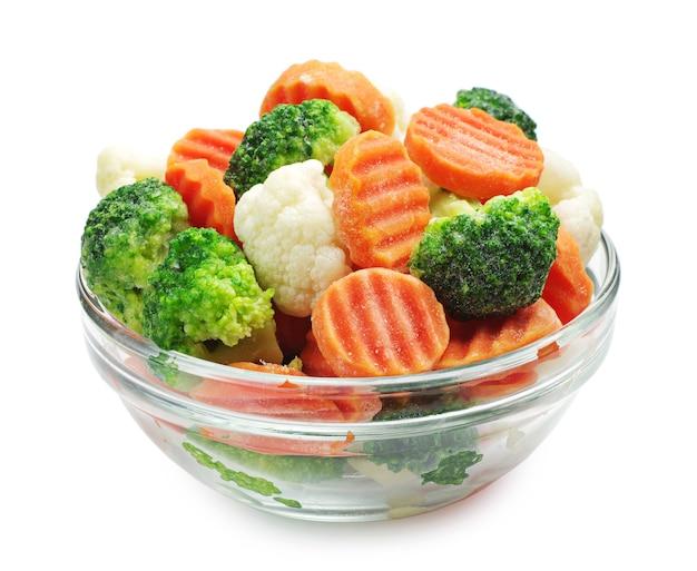 Замороженные овощи в стеклянной миске на белом фоне