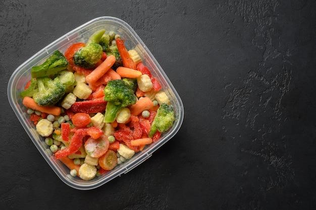 Замороженные овощи в контейнере на черном фоне, вид сверху