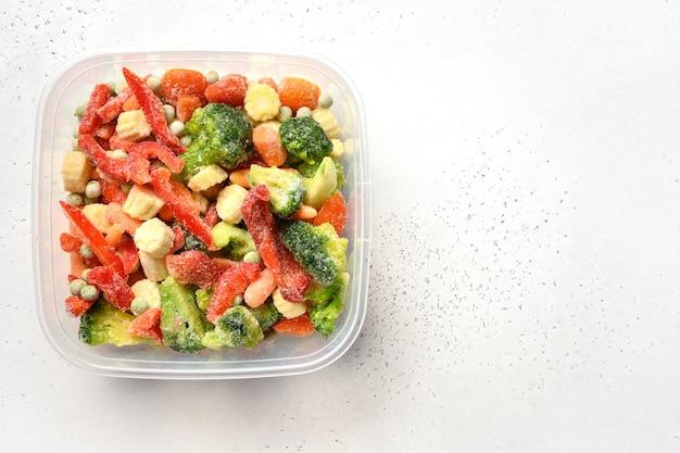 Замороженные овощи в контейнере на белом фоне копией пространства