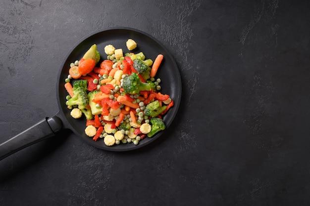 Замороженные овощи в сковороде на черном фоне, вид сверху