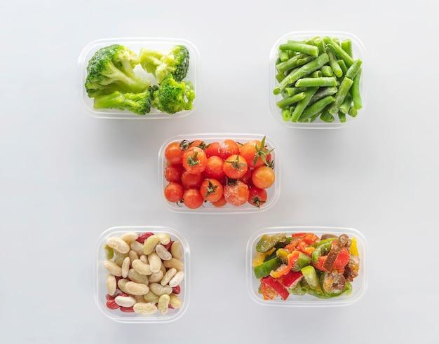 白い背景の上のプラスチック容器で冷凍野菜。フラットレイ。冷凍ブロッコリー、インゲン、ミニトマト、豆、ピーマン。