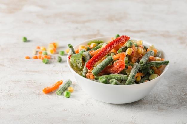 冷凍野菜。明るい背景に白いボウルに野菜、インゲン、カリフラワーのミックス。
