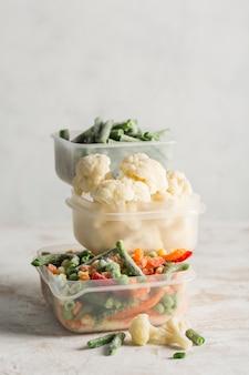 冷凍野菜。野菜、いんげん豆、カリフラワーをさまざまなプラスチック容器に混ぜて、明るい背景で凍結します。