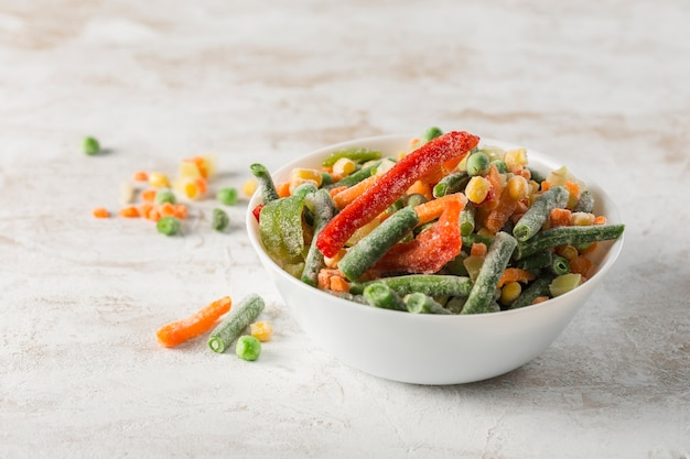 Frozen vegetables. mix of vegetables, string beans and cauliflower in a white bowl on a light background.
