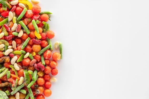 コピースペースのある白い背景の冷凍野菜。雪と氷で覆われた冷凍野菜の盛り合わせ。