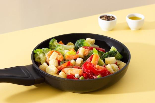 Замороженные овощи на сковороде: перец, морковь, брокколи, мини-кукуруза, помидоры и зеленый горошек, перец и оливковое масло на заднем плане.