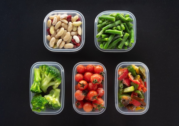 Frozen vegetables in plastic containers on black background. frozen broccoli, green beans, cherry tomatoes, beans and bell pepper.