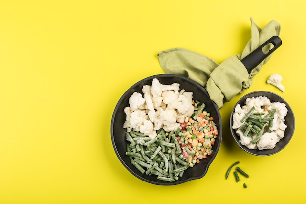 Frozen vegetables: string beans, cauliflower and a mix of vegetables in a black pan with a napkin and in a plate on a bright yellow background.