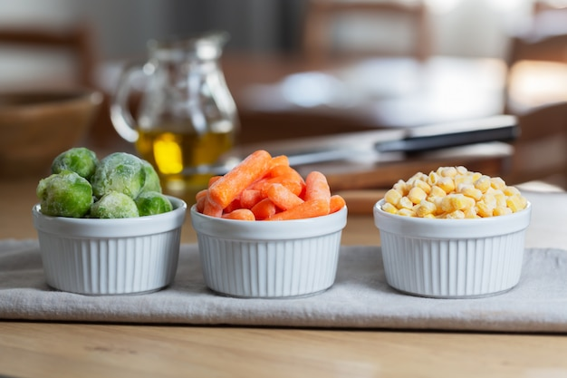 Frozen vegetables such as baby carrot and and brussels sprouts in the bowls on the kitchen table, horizontal
