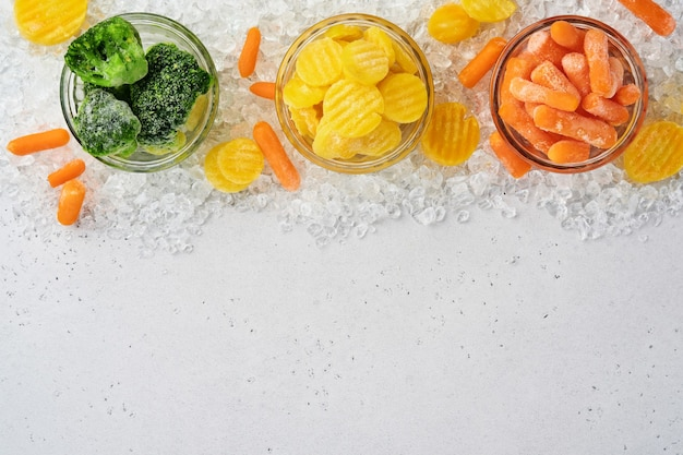 Замороженные овощи, такие как зеленая брокколи, желтый цвет и морковь, в стеклянных мисках на льду и бетонном сером столе с копией пространства.