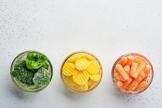 Frozen vegetables such as green broccoli, yellow and baby carrot in glass bowls on ice and concrete gray table with copy space.