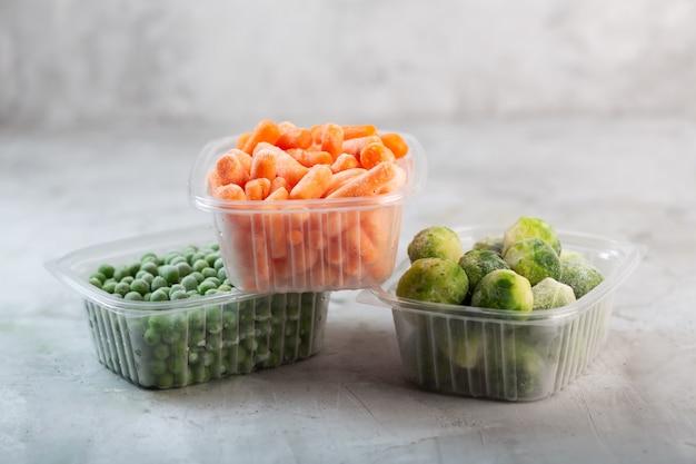 Замороженные овощи, такие как зеленый горошек, брюссельская капуста и морковь в пластиковых коробках на бетонном сером пространстве