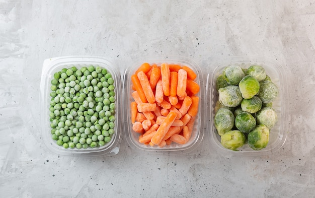 Frozen vegetables such as green peas, brussels sprouts and baby carrot in the storage boxes on the concrete gray space